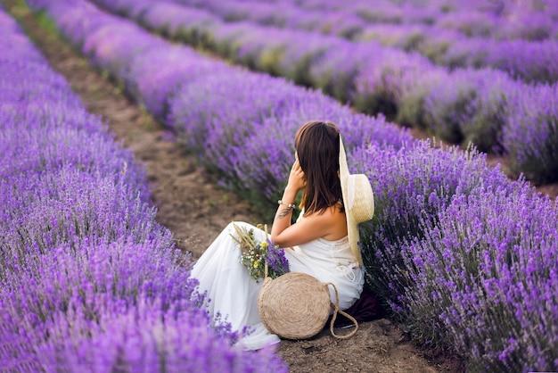 Mooie vrouw in een witte jurk en hoed verzamelt lavendel. zomerfoto's.