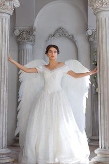 Mooie vrouw in een witte jurk met engelenvleugels op haar rug. het staat in een prachtig decor tegen de muur.