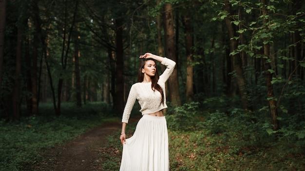 Mooie vrouw in een witte jurk verkent een prachtig bos