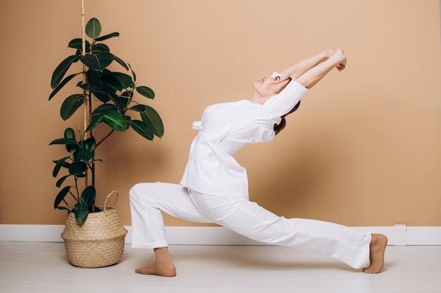 Mooie vrouw in een witte kimono doet thuis ochtendoefeningen