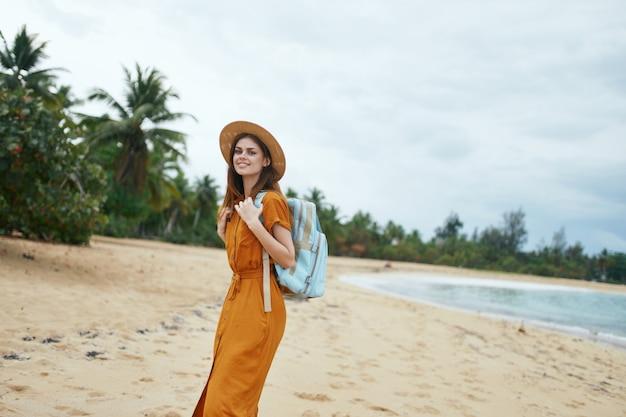 Mooie vrouw in een zomerjurk met een rugzak op haar rug lopen