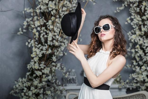 Mooie vrouw in een zwarte hoed, zonnebril en een witte jurk tegen vintage wit voorjaar interieur