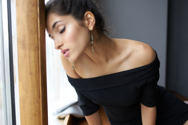 Mooie vrouw in een zwarte jurk bij het raam poseren fashion model