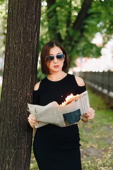 Mooie vrouw in een zwarte jurk in een park met een brandende krant in haar handen