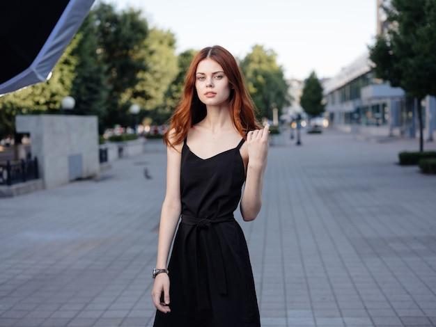 Mooie vrouw in een zwarte jurk loopt in het park en groene bomen op de achtergrond