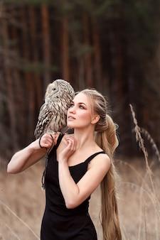 Mooie vrouw in een zwarte jurk met een uil op zijn arm. blonde met lang haar in de natuur met een uil. romantisch delicaat beeld van een meisje