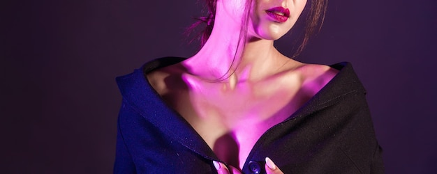 Mooie vrouw in een zwarte jurk met studiolichten