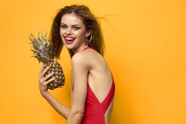 Mooie vrouw in een zwembroek, rode zwembroek, grappig beeld op een gele ruimte met tropische vruchten kokosnoot en ananas