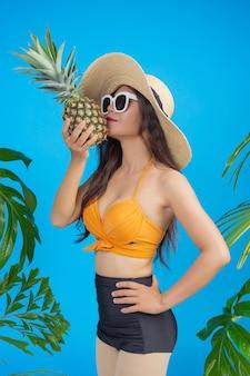 Mooie vrouw in een zwempak die een ananas op blauw houdt