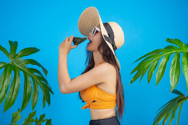 Mooie vrouw in een zwempak die een watermeloen op blauw houden