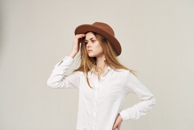 Mooie vrouw in elegant de stijlmanierlicht van het hoeden wit overhemd