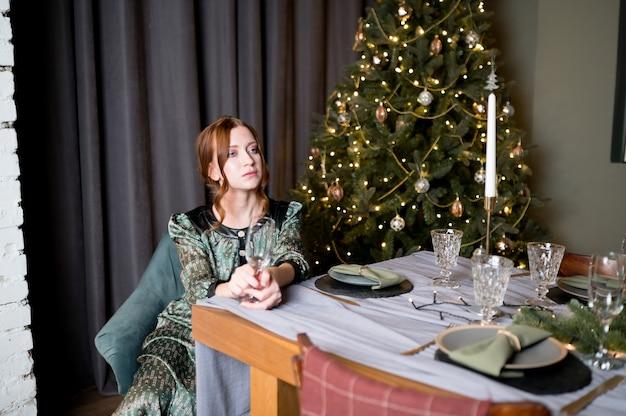 Mooie vrouw in elegante jurk op de achtergrond van luxe kerstboom in een kamer rijk interieur