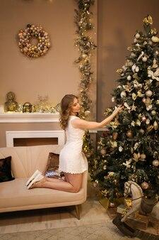 Mooie vrouw in elegante jurk siert de kerstboom met speelgoed in een luxe interieur