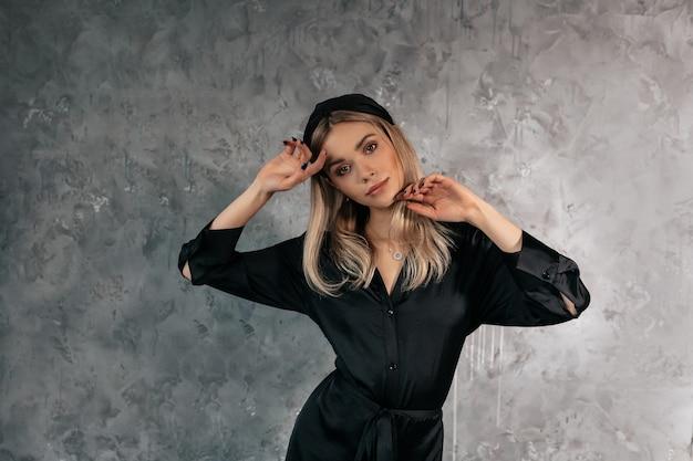 Mooie vrouw in feestelijke jurk die gevoelig op grijs poseren