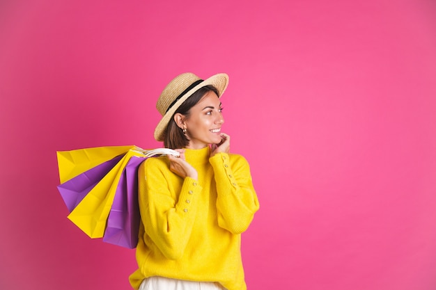 Mooie vrouw in felgele trui en strohoed op roze boodschappentassen, blij opgewonden, vreugdevolle geïsoleerde ruimte voor tekst