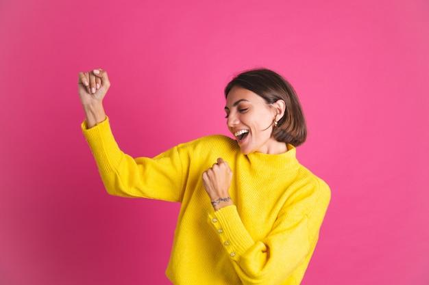 Mooie vrouw in felgele trui geïsoleerd op roze blij opgewonden dansende bewegende smile