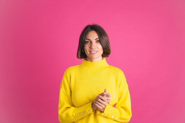 Mooie vrouw in felgele trui geïsoleerd op roze blik naar voren met zelfverzekerde glimlach