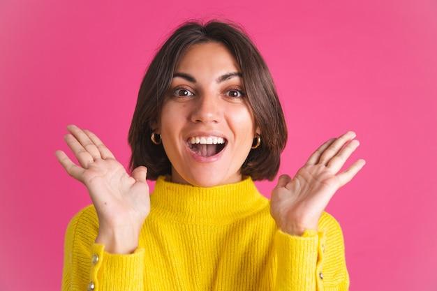 Mooie vrouw in felgele trui geïsoleerd op roze schreeuwen opgewonden vreugdevol