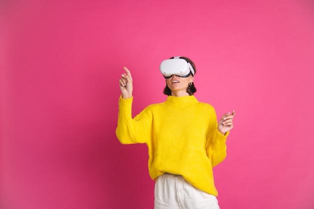 Mooie vrouw in felgele trui op roze in virtual reality-bril, blij punt links met vinger naar lege ruimte