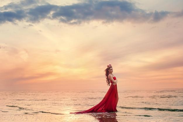 Mooie vrouw in fladderende rode jurk op zee golf bij zonsondergang.