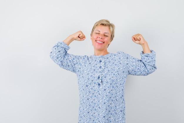 Mooie vrouw in gedessineerde blouse die winnaargebaar toont en gelukkig, vooraanzicht kijkt.