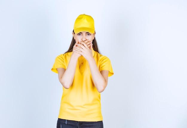 Mooie vrouw in geel t-shirt en pet geschokt over iets op witte achtergrond.