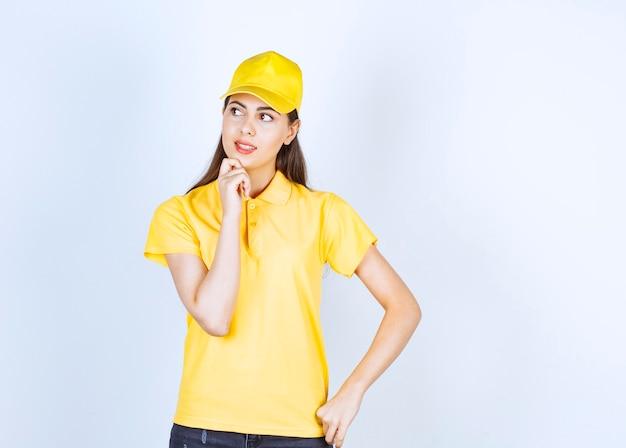 Mooie vrouw in geel t-shirt en pet kijken naar haar kant op witte achtergrond.