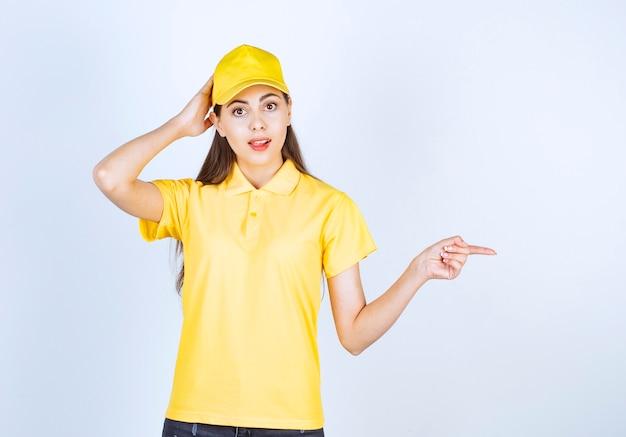 Mooie vrouw in geel t-shirt en pet wijzend naar ergens op een witte achtergrond.
