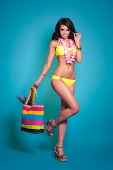 Mooie vrouw in gele bikini met zak op het strand