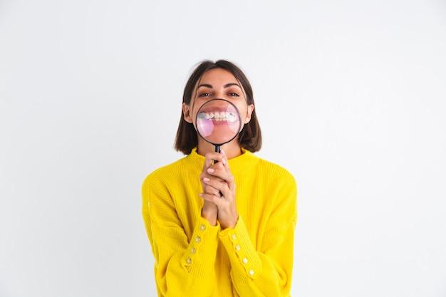 Mooie vrouw in gele trui op wit hield vergrootglas gelukkig positief met witte sneeuwtanden glimlach