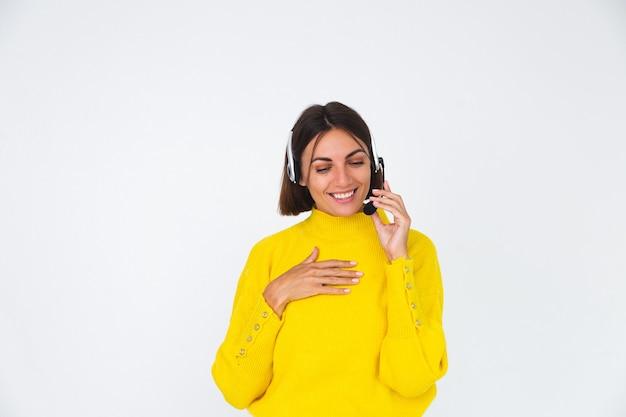 Mooie vrouw in gele trui op witte manager met koptelefoon, blij met een gesprek met de glimlach van de klant, lach