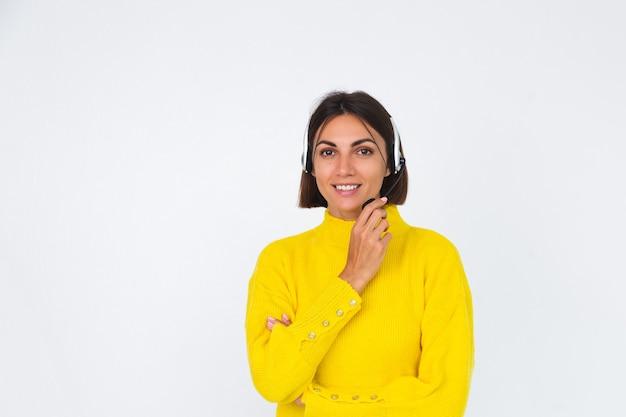 Mooie vrouw in gele trui op witte manager met koptelefoon, blije positieve gastvrije glimlach