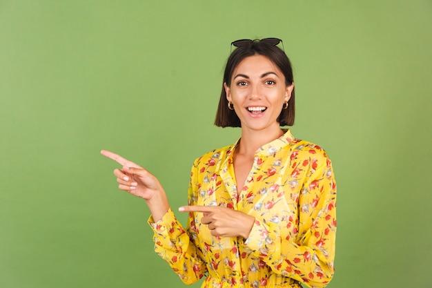 Mooie vrouw in gele zomerjurk en zonnebril, groene studio, opgewonden, vrolijke wijsvinger links
