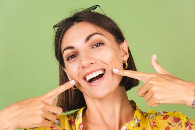 Mooie vrouw in gele zomerjurk en zonnebril, groene studio, opgewonden, vrolijke wijsvinger op perfecte witte tanden