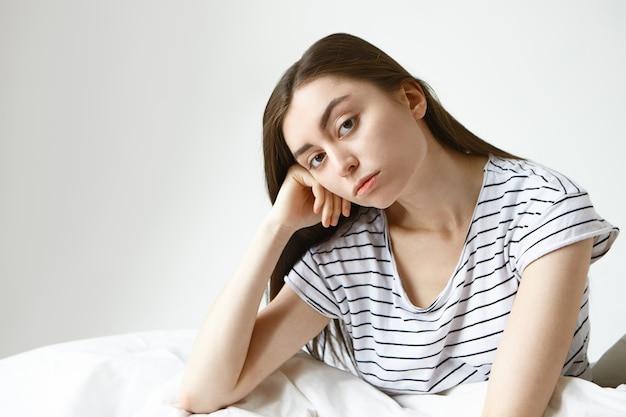 Mooie vrouw in gestreepte pyjama die ongelukkige uitdrukking heeft verveeld, die met hand onder haar wang zit terwijl zittend op bed