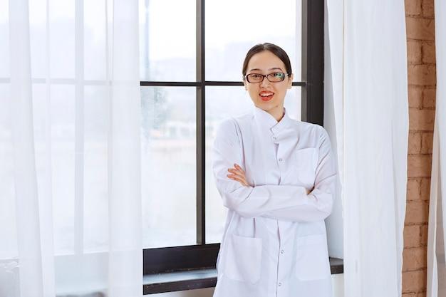 Mooie vrouw in glazen en laboratoriumjas staande met gekruiste armen in de buurt van raam.