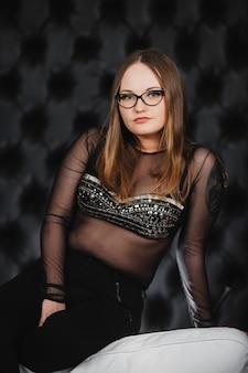 Mooie vrouw in glazen en zwarte broek poseren