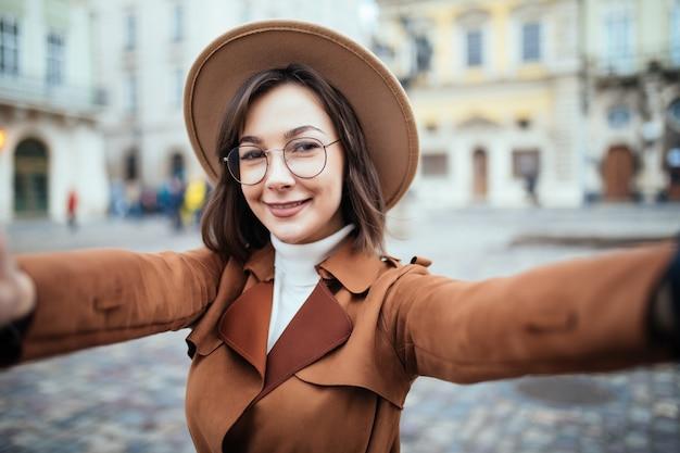 Mooie vrouw in glazen neemt selfie terwijl ze haar telefoon in de stad