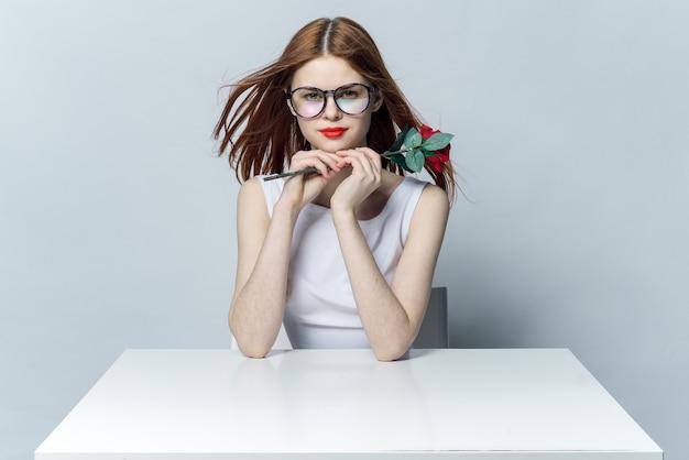 Mooie vrouw in glazen zit aan een tafel met rode roos