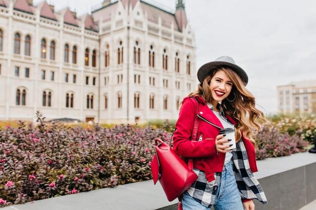 Mooie vrouw in goed humeur draagt een geruit overhemd dat zich dichtbij oud paleis met glimlach bevindt