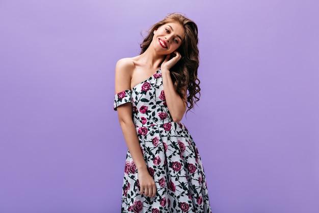Mooie vrouw in goed humeur vormt op paarse achtergrond. krullend schattig meisje in kleurrijke trendy jurk glimlachend op geïsoleerde achtergrond.