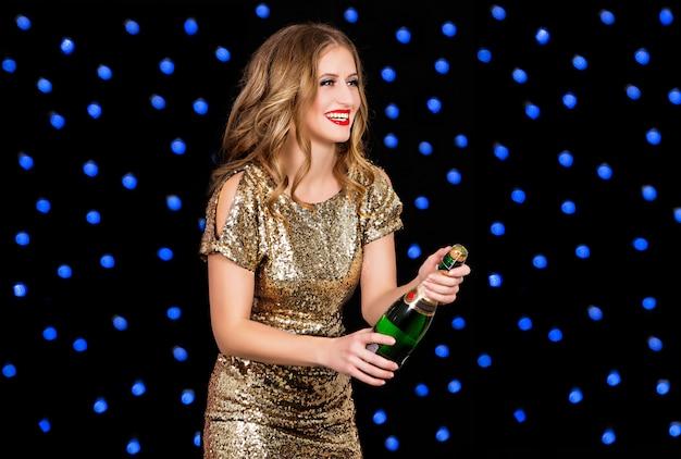 Mooie vrouw in gouden jurk met champagne op zwarte achtergrond