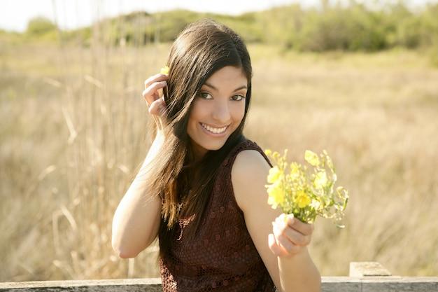 Mooie vrouw in gouden openlucht, gele bloem