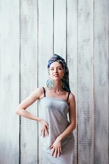 Mooie vrouw in grijze jurk en blauwe hoofddoek op een afrikaanse manier