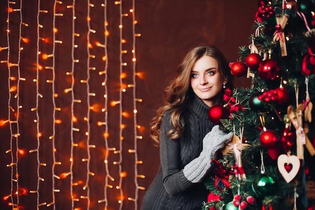Mooie vrouw in grijze kleding die zich tegen verfraaide kerstmisboom bevindt.