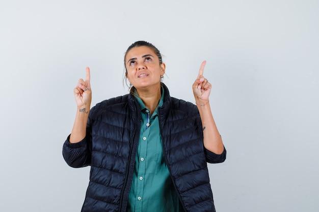 Mooie vrouw in groen shirt, zwarte jas die met wijsvingers omhoog wijst, naar boven kijkt en er gelukkig uitziet, vooraanzicht.