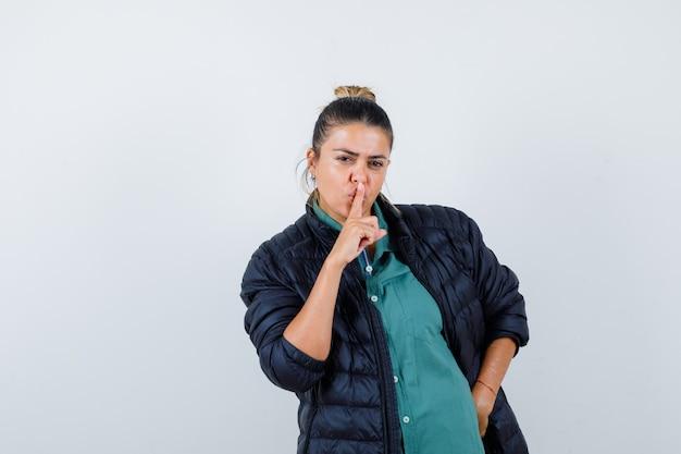 Mooie vrouw in groen shirt, zwarte jas die stiltegebaar toont, met de hand op de heup en er serieus uitziet, vooraanzicht.