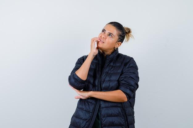 Mooie vrouw in groen shirt, zwarte jas staande in denkende pose, hand in de buurt van mond en peinzend kijkend, vooraanzicht.