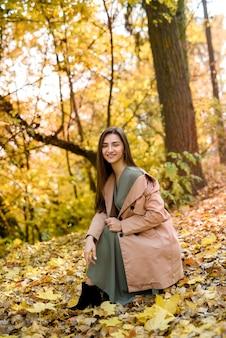 Mooie vrouw in groene jurk poseren in herfst park met gele bladeren