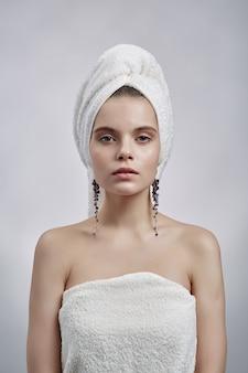 Mooie vrouw in handdoek en oorringen